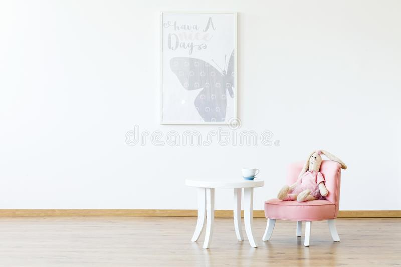 Plush toy on pink chair at table in white girl`s room interior w stock photos