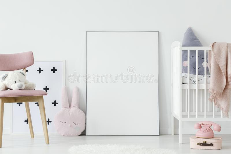 Plush toy on pink wooden chair next to empty poster with mockup royalty free stock photos