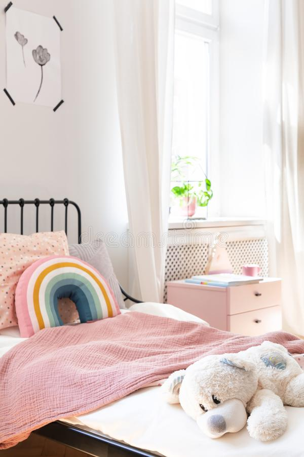 Plush toy and rainbow pillow on bed in white kid`s bedroom interior with window. Real photo stock photos