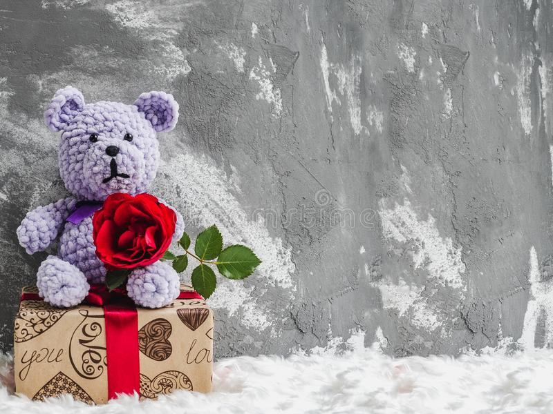 Plush toy, red rose and a gift box. Bright plush toy, blooming red rose, white plaid and a gift box tied with a ribbon. Studio photo. Close-up, indoors royalty free stock photography