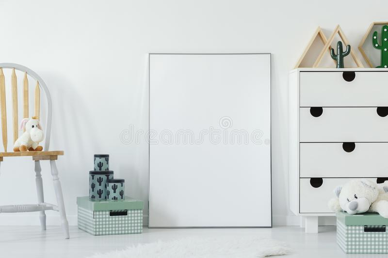 Plush toy on wooden chair next to white empty poster with mockup stock images