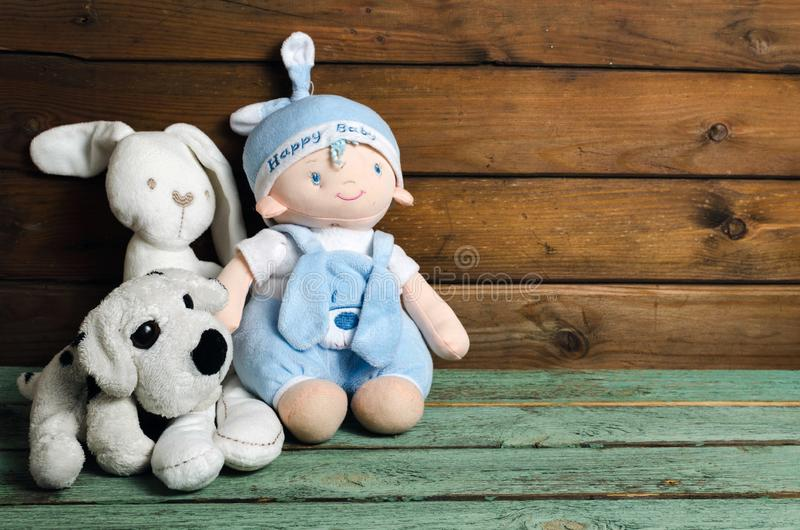 Plush toys. Bunny, dog and small baby sitting on wooden table royalty free stock photo