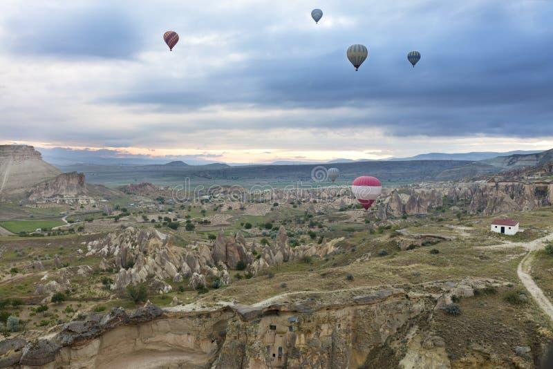 Plusieurs ballons volent au-dessus des vallées dans Cappadocia photographie stock libre de droits