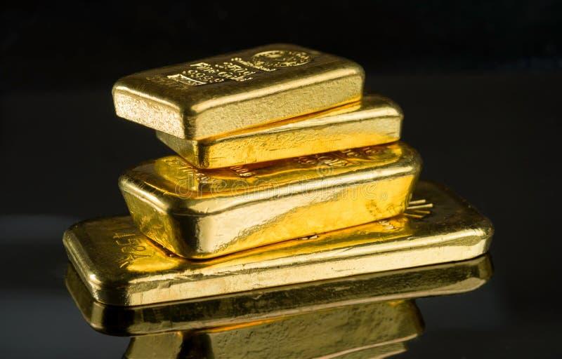 Plusieurs barres d'or de poids différent sur une surface foncée de miroir images stock