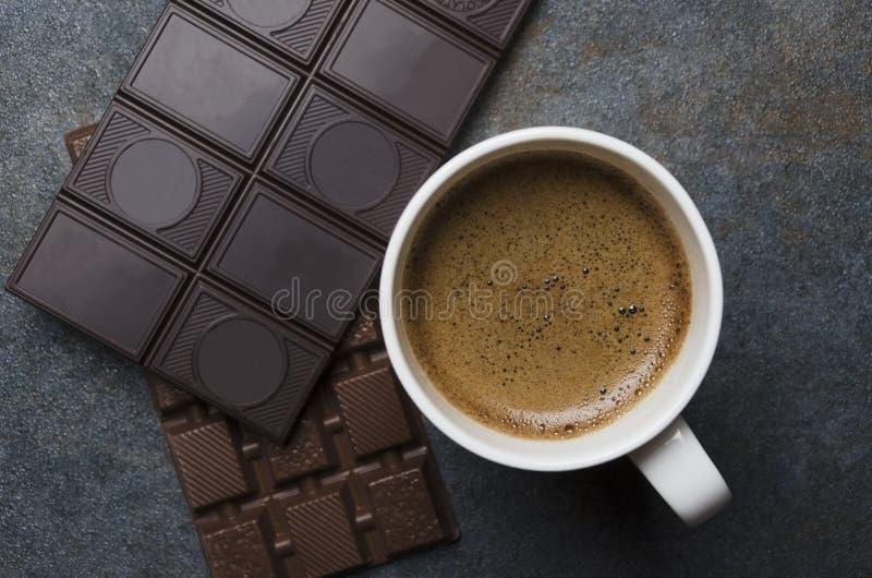 Plusieurs barres de chocolat et café savoureux chaud avec la grande mousse brune photos libres de droits