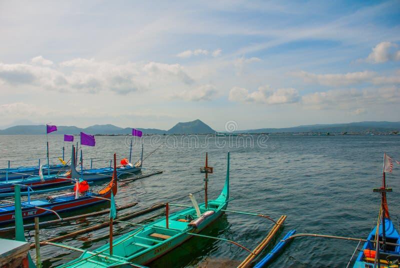 Plusieurs bateaux philippins traditionnels de tangon ou ` de banca de ` ont amarré à un pilier en bois sur le rivage du lac Taal, images libres de droits