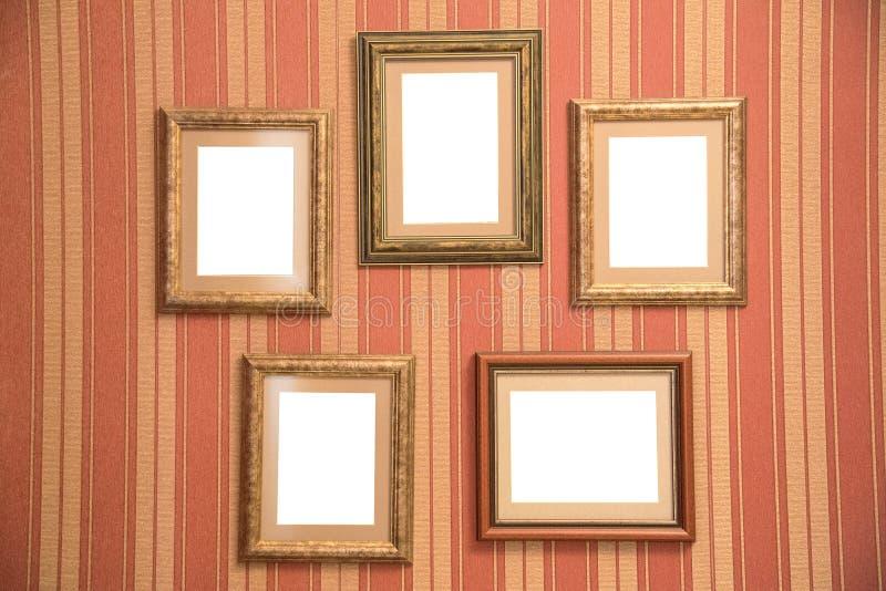 Plusieurs beaux cadres pour des photos d'or sur un wal rouge rayé photographie stock libre de droits