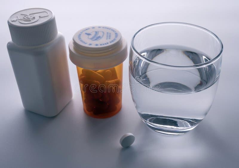 Plusieurs bouteilles avec le médicament divers à côté d'un verre de l'eau photographie stock libre de droits