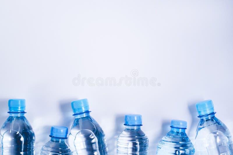 Plusieurs bouteilles d'eau potables sur le fond blanc images libres de droits