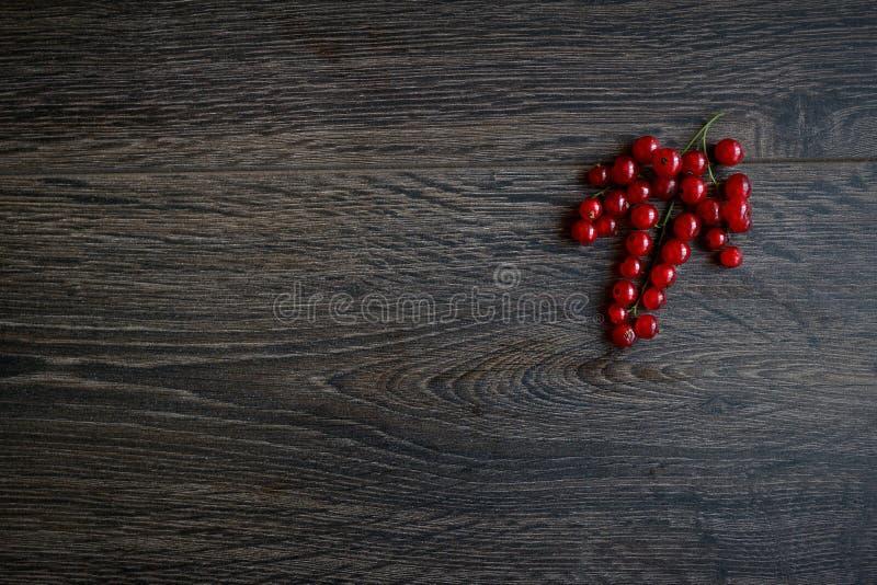 Plusieurs branches de groseille rouge se trouvent admirablement sur une base en bois de chêne Beaucoup d'espace libre, texture images stock