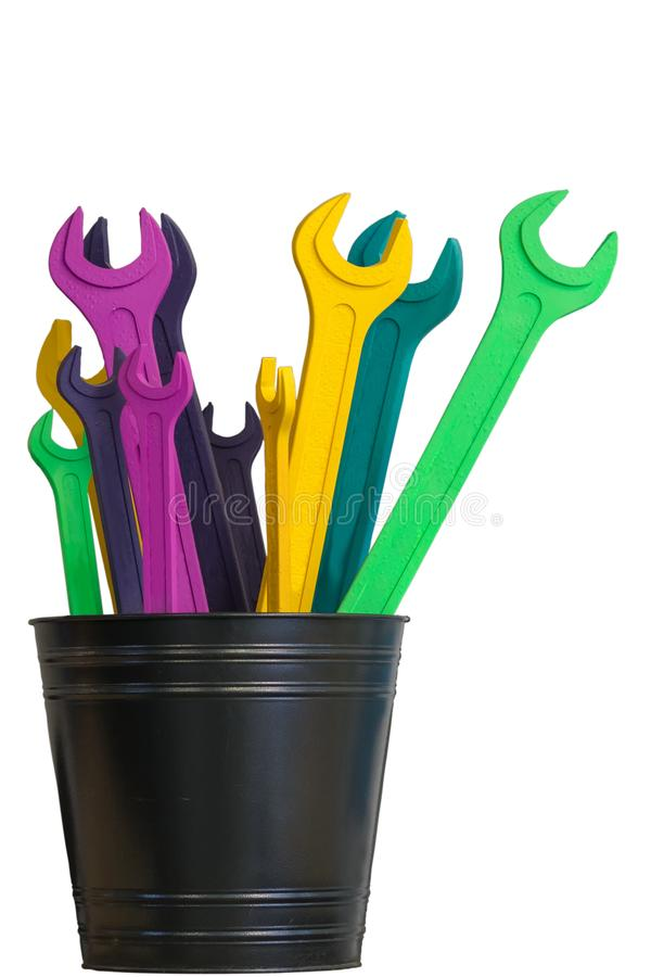 Plusieurs clés à fourche colorées se tiennent dans un seau noir d'isolement sur un fond blanc image stock