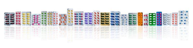 Plusieurs de pilules colorées dans des habillages transparents dans une rangée sur le fond blanc avec l'espace de copie Industrie photographie stock