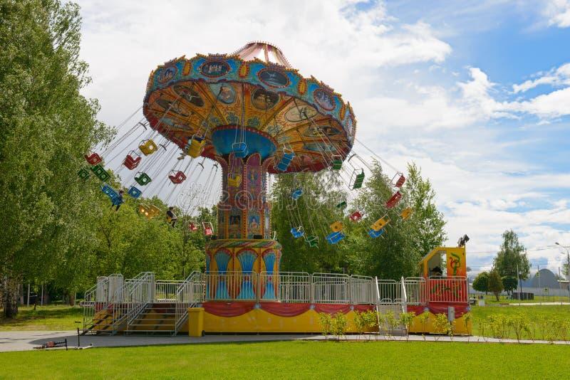 Plusieurs enfants montent un carrousel en parc d'attractions images stock