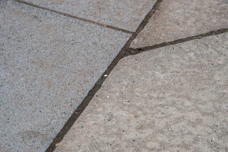 Plusieurs fissures entre les blocs de trottoir concret Certains sont perpendiculaires et on va sur un angle image libre de droits