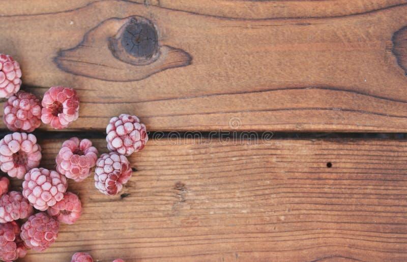 Plusieurs framboises surgelées, couvertes de fruit, se trouvent sur le fond en bois image stock