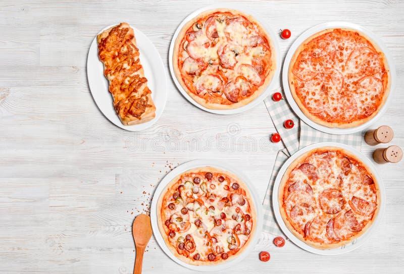 Plusieurs genres de pizza sont tirés sur un fond en bois clair photographie stock