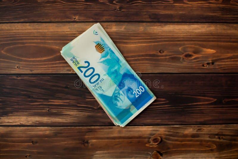 Plusieurs nouveaux billets de banque en valeur 200 nouveaux shekels israéliens sur un fond en bois images libres de droits