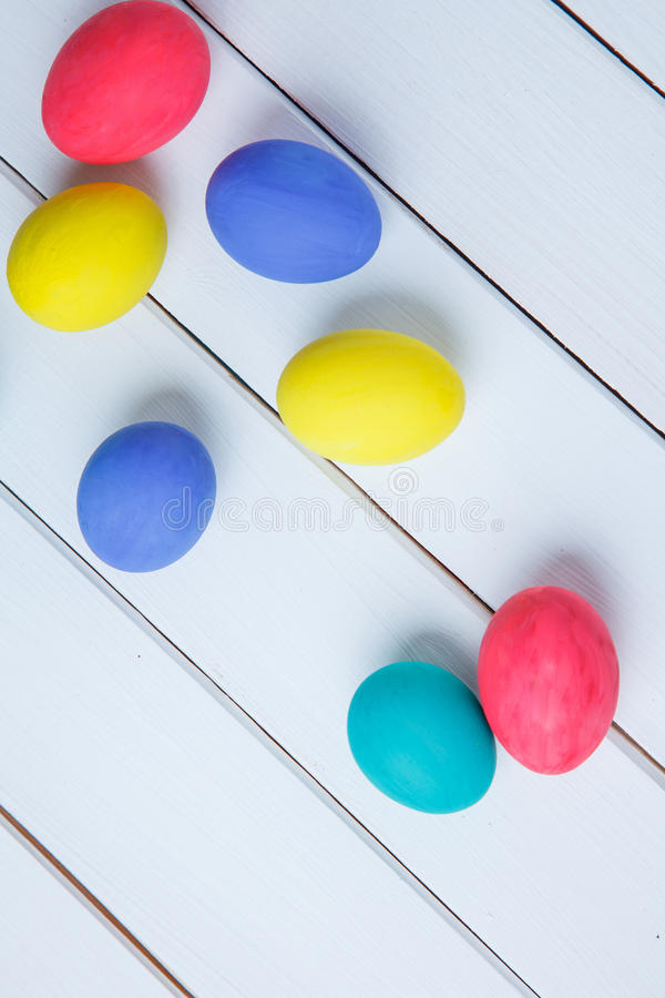 Plusieurs oeufs colorés sur une table blanche Joyeuses Pâques image libre de droits