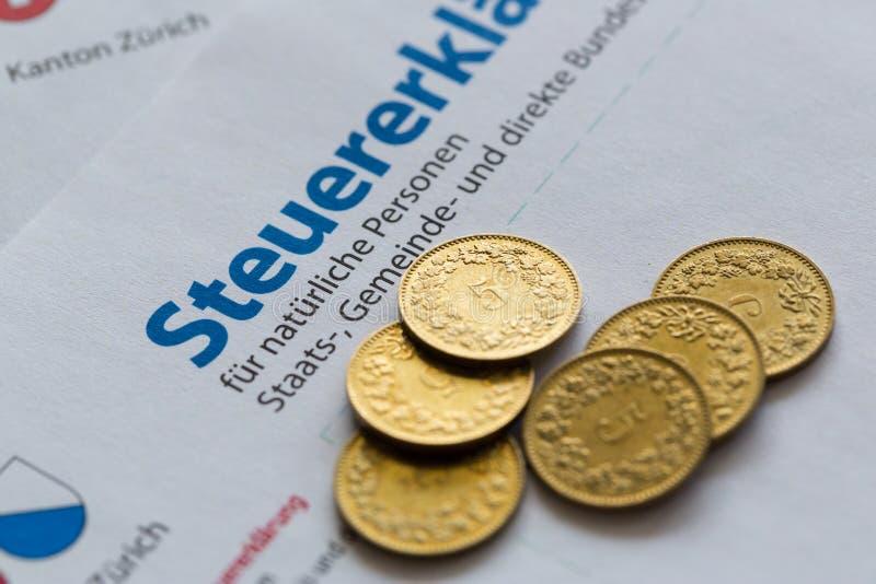 Plusieurs pièces de monnaie d'or sur le formulaire de déclaration suisse d'impôts, Zurich photo stock
