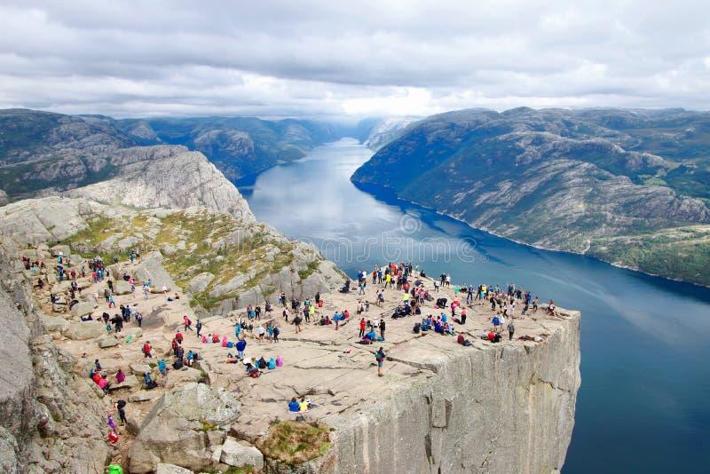 Plusieurs randonneurs appréciant les vues dans le sommet de la roche Preikestolen, Norvège de pupitre photo libre de droits