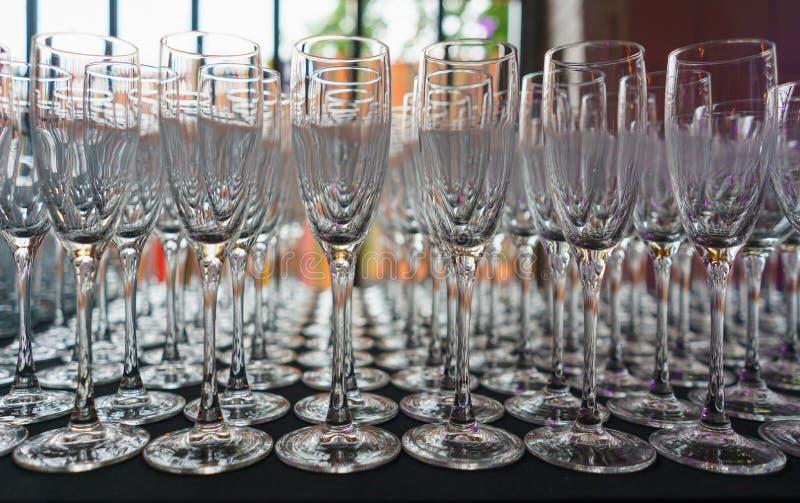Plusieurs rangées dégagent les verres transparents et propres pour le vin et le champagne sur le compteur préparé pour des boisso photos stock
