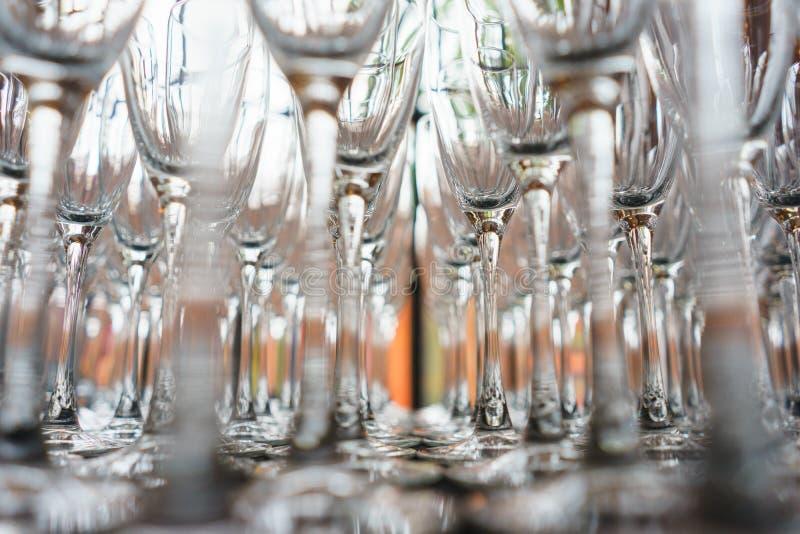 Plusieurs rangées dégagent les verres transparents et propres pour le vin et le champagne sur le compteur préparé pour des boisso photographie stock