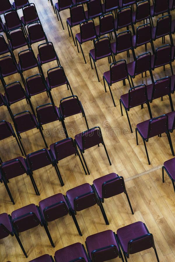 Plusieurs rangées des chaises en plastique vides dans l'assistance ont préparé les journalistes et les spectateurs d'étudiants d' photo stock