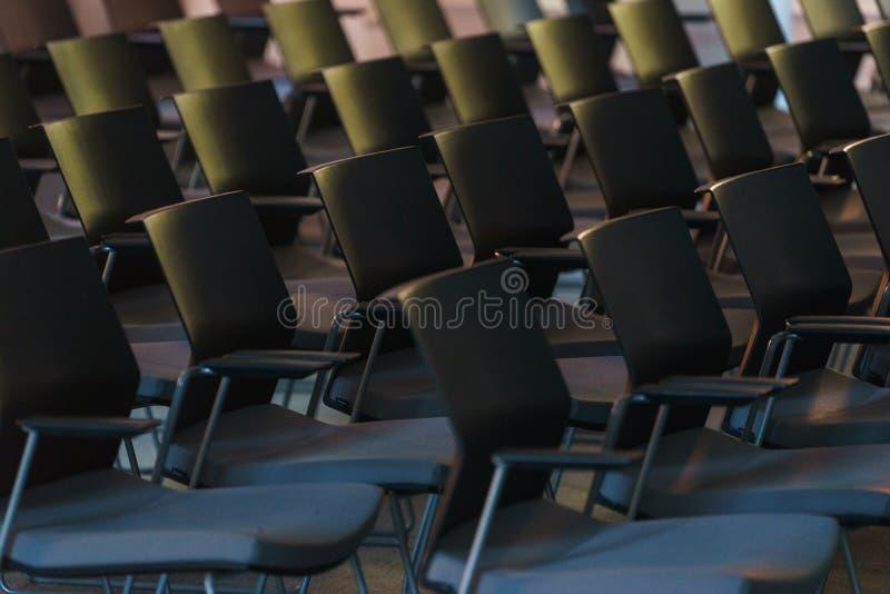 Plusieurs rangées des chaises en plastique vides dans l'assistance se sont préparées au discours du ` s de haut-parleur devant de photographie stock libre de droits