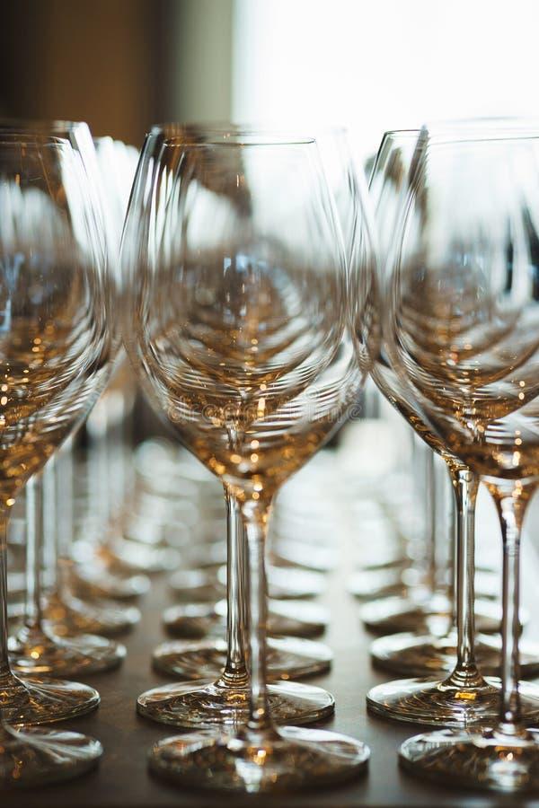 Plusieurs rang?es clairement, verres propres pour le vin et champagne sur le compteur pr?par? pour des boissons photo stock