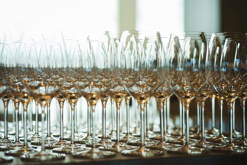 Plusieurs rang?es clairement, verres propres pour le vin et champagne sur le compteur pr?par? pour des boissons photos stock