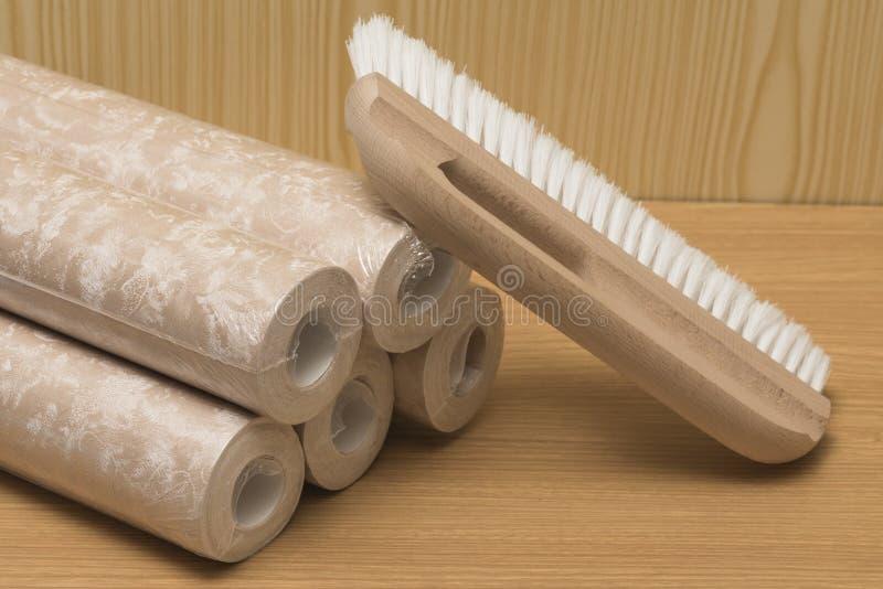 Plusieurs rouleaux de papier peint et d'une brosse pour appliquer la colle photographie stock