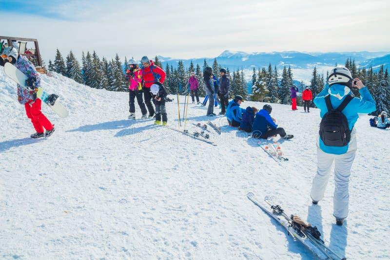 Plusieurs skieurs se reposent sur le dessus de la montagne Un groupe de personnes dans des costumes de ski se reposant sur la nei images stock