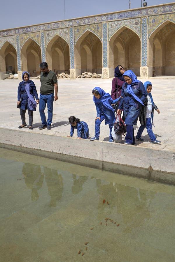 Plusieurs touristes iraniens observant le poisson rouge qui nagent dans l'étang, IR image stock