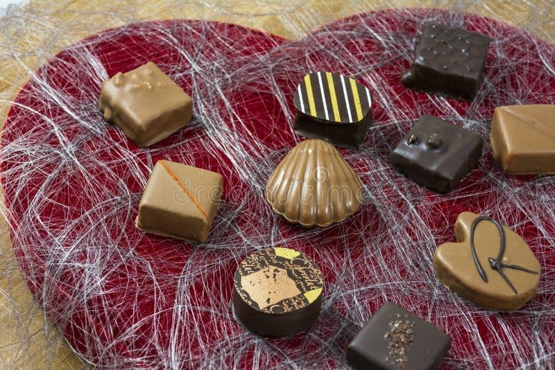 Plusieurs traient et les bonbons au chocolat foncés sur le coeur rouge forment le fond image libre de droits