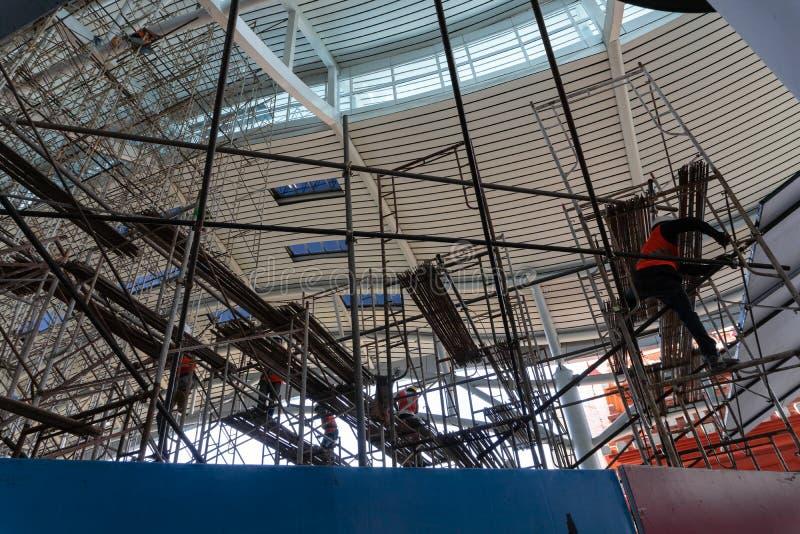 Plusieurs travailleurs s'chargeaient de l'échafaudage dans un bâtiment pour faire des réparations et l'entretien dans le secteur  images libres de droits