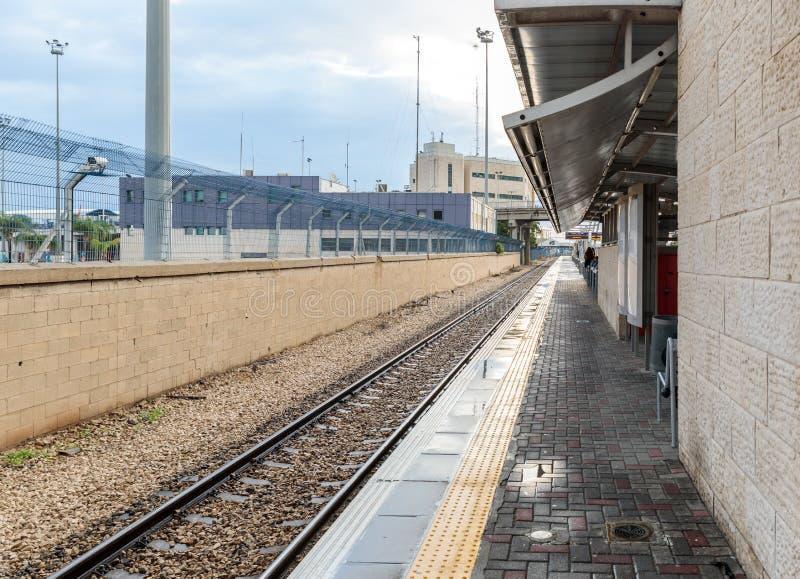 Plusieurs voyageurs attendent le train sur la plate-forme vide de la gare ferroviaire de Mirkaz Shmona à Haïfa, Israël photo stock