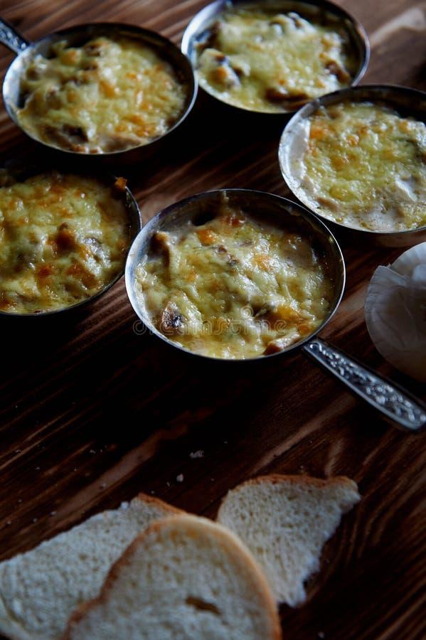 Plusieurs zhuleny des champignons ont fait cuire au four en crème avec du fromage Dans le cocotte de fer images libres de droits