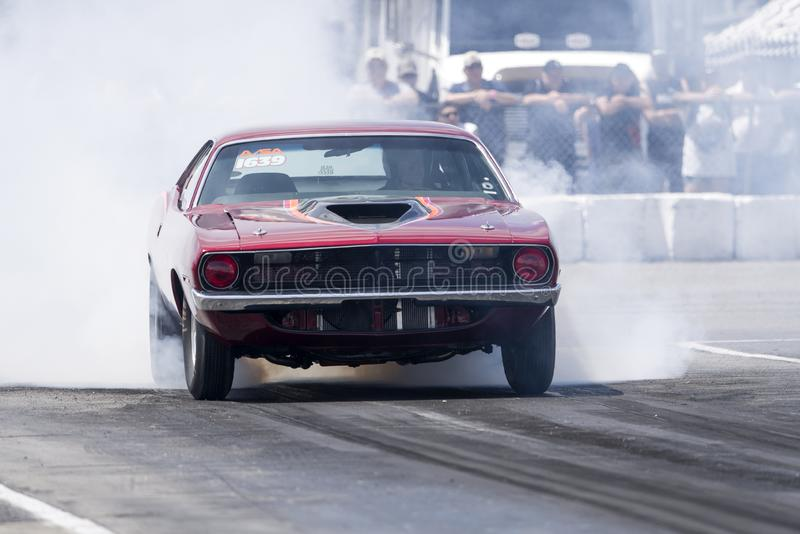 Plymouth-cuda die rook maken op het rasspoor bij de beginnende lijn tonen stock foto's
