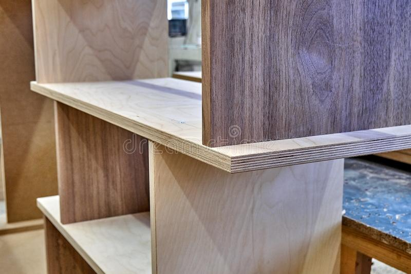 Plywood bookshelves. Production of wood furniture. Furniture manufacture. Close-up. Beautiful professionally made plywood bookshelves in process of production in stock image