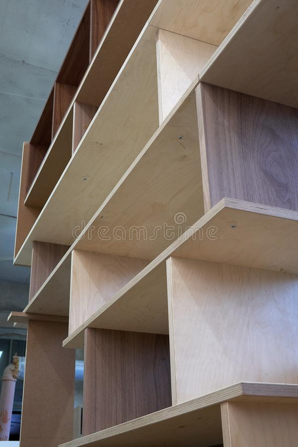 Plywood bookshelves. Production of wood furniture. Furniture manufacture. Close-up. Beautiful professionally made plywood bookshelves in process of production in royalty free stock images