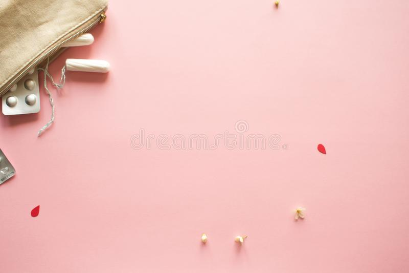 PMS en het kritieke dagenconcept Pijnpillen en persoonlijke verzorgingproducten, roze achtergrond stock afbeeldingen