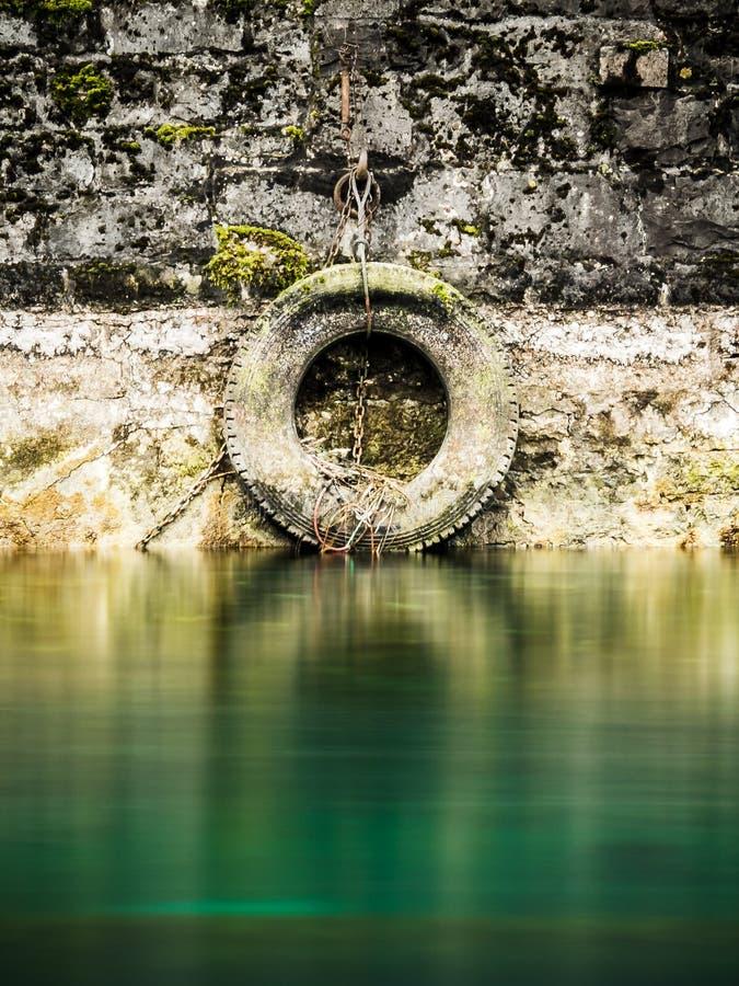 Pneu antique de véhicule employé pour amarrer des bateaux sur la rivière le Rhône, Genève Suisse image libre de droits