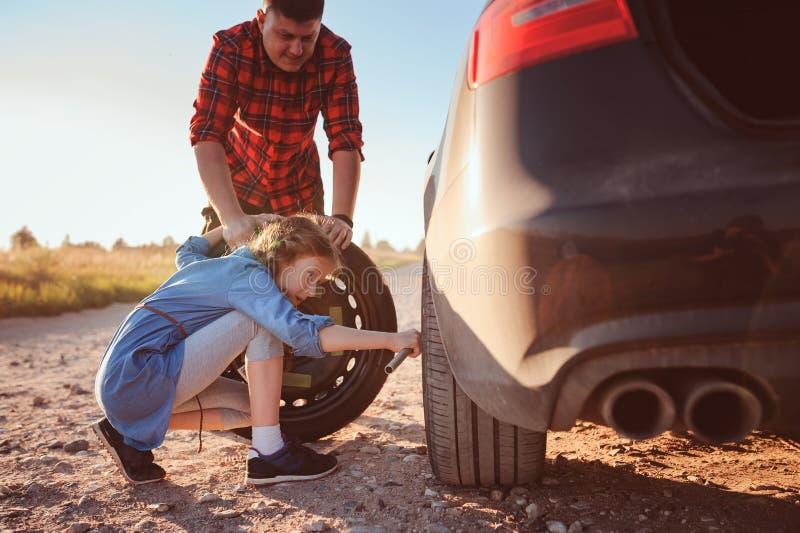Pneu cassé changeant de père et de fille pendant le voyage par la route rural d'été photo libre de droits