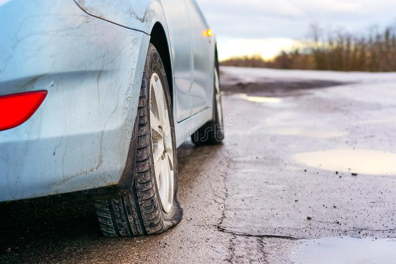 Pneu crevé de voiture bleue sur la réparation de attente de route Fuite de pneu de voiture en raison du broyage de clou images libres de droits