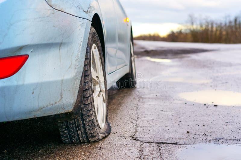 Pneu crevé de voiture bleue sur la réparation de attente de route Fuite de pneu de voiture en raison du broyage de clou photographie stock libre de droits