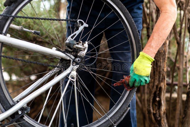 Pneu de limpeza da bicicleta do homem para a estação nova foto de stock