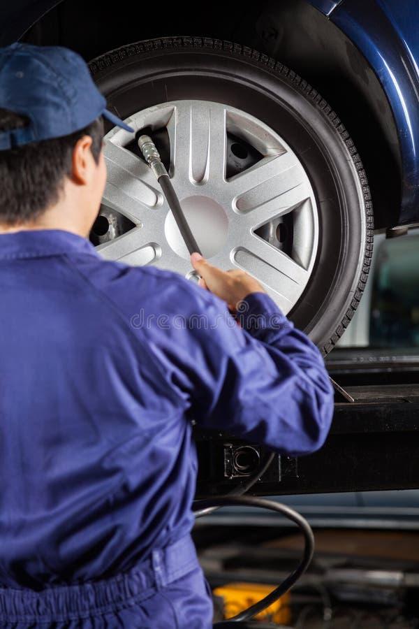 Pneu de voiture de Filling Air Into de technicien au garage image stock