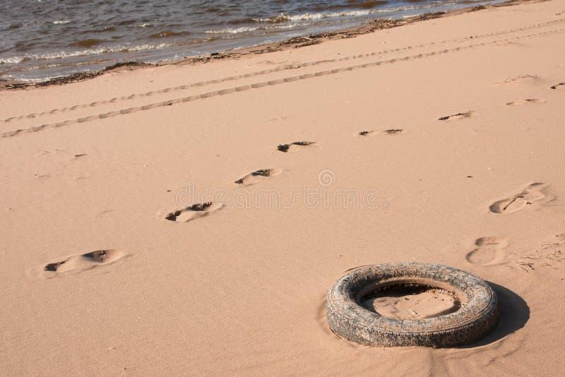 Pneu de voiture de pollution dans le sable sur la plage près de l'eau image stock