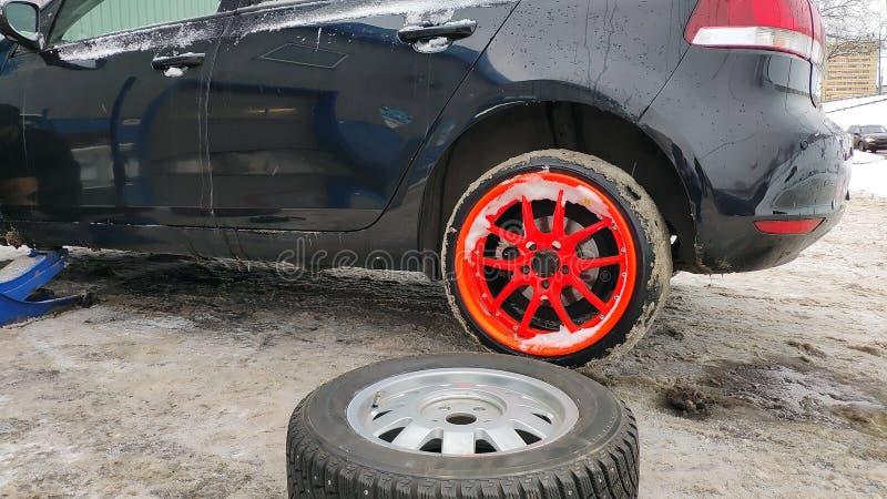 Pneu do inverno que cabe na rua Serviço da roda, de reparo do pneu verão, e de mudança aos pneus do inverno Carro preto levantado fotografia de stock royalty free