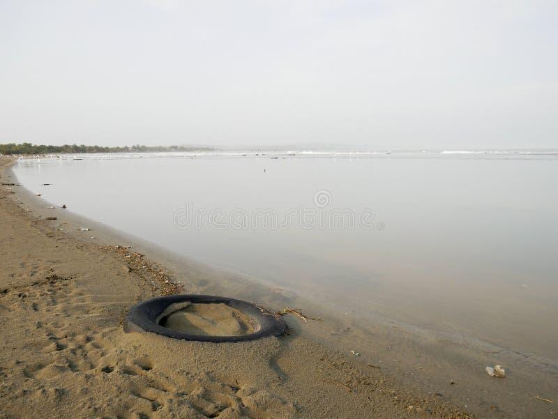 Pneu enterrado na costa de uma praia das caraíbas perto de cartagena Colômbia com os pássaros na poluição do fundo imagem de stock